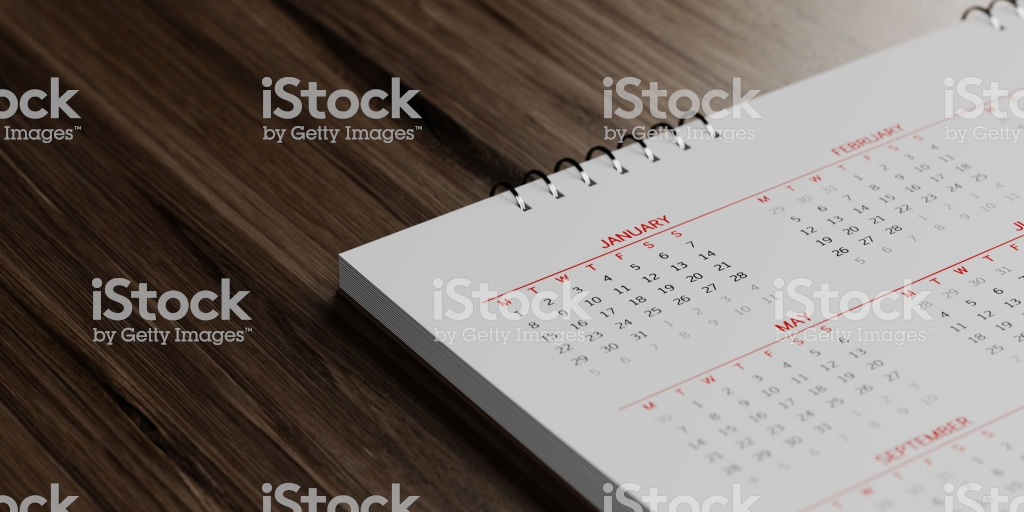 White calendar on brown reflective wood surface. January, May and February months are visible. Panoramic composition with copy space. Calendar and reminder concept with selective focus.